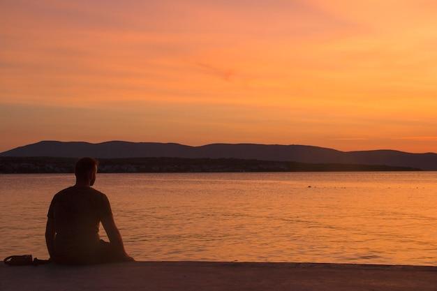 Silhouet van een man zittend op een pier bij zonsondergang van de zee