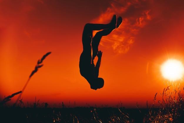 Silhouet van een mannelijke atleet die en salto's springt doet