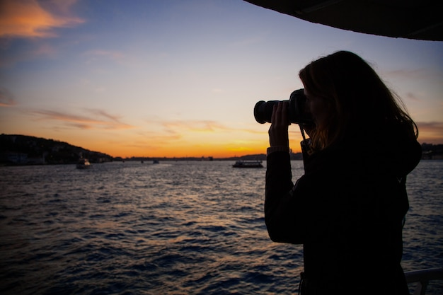 Silhouet van een meisje dat een foto van de boot op het bord van een veerboot bij zonsondergang in istanbul