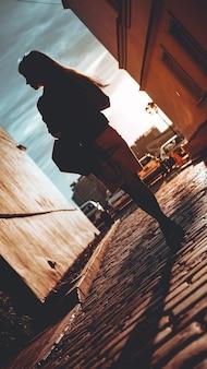 Silhouet van een meisje dat in de stralen van de zon op een stenen bestrating in een europese stad loopt, het concept van een gelukkige reis, een vakantie in europa