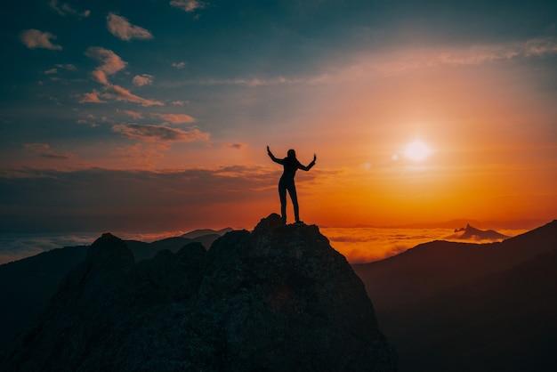 Silhouet van een meisje dat op een rotsachtige piek danst bij zonsondergang