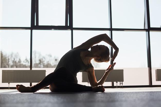 Silhouet van een meisje dat yoga doet tegen de achtergrond van panoramische ramen in een moderne yogastudio