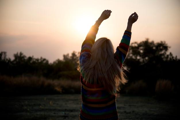 Silhouet van een meisje die zich uitstrekt in de ochtend