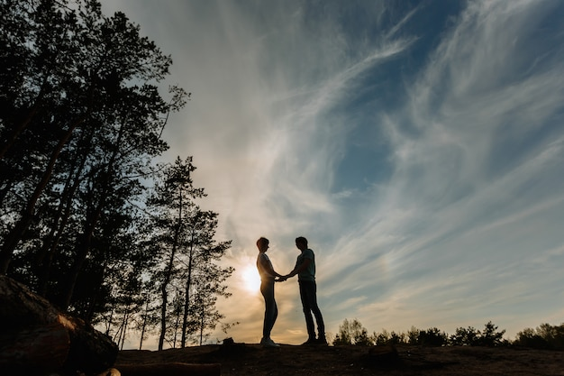 Silhouet van een meisje en een man hand in hand tegen de achtergrond van de zonsondergang