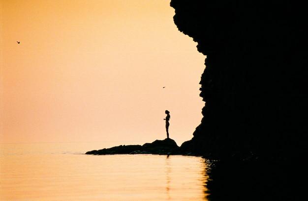 Silhouet van een meisje in de buurt van de zee bij zonsondergang