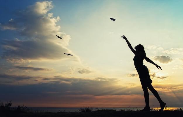 Silhouet van een meisje in de zomerjurk lanceert een papieren vliegtuigje op een achtergrond van een prachtige zonsondergang