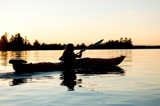 Silhouet van een meisje kajakken in een meer, lake of the woods, ontario, canada