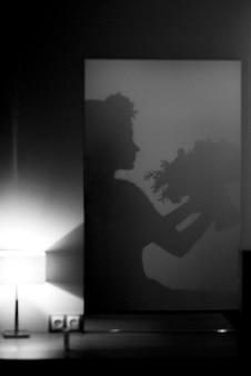 Silhouet van een meisje met een boeket in haar handen in de spiegel