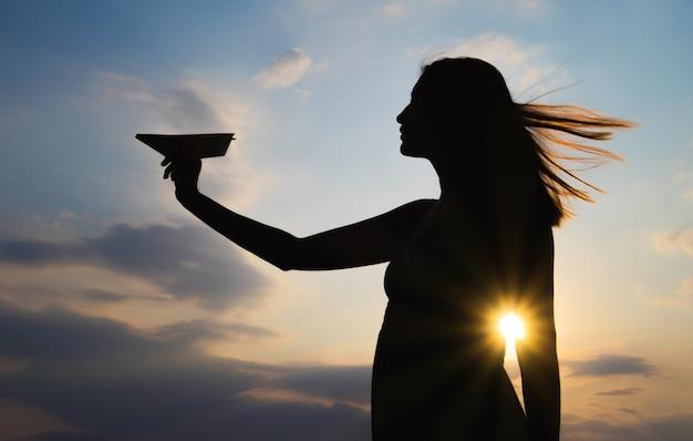 Silhouet van een meisje met een papieren vliegtuigje in hand over zonsondergang achtergrond