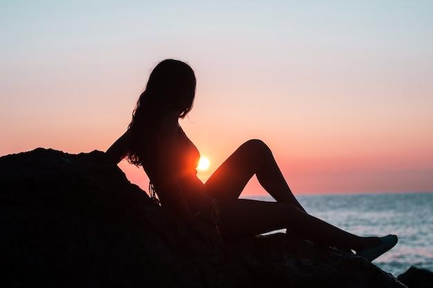 Silhouet van een meisje op het strand tijdens zonsopgang