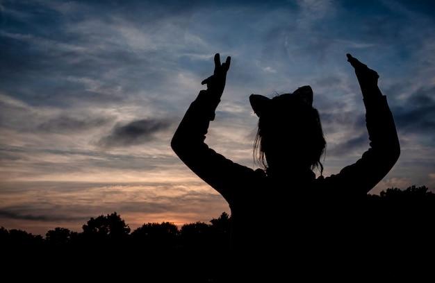 Silhouet van een meisje tegen de zonsondergang