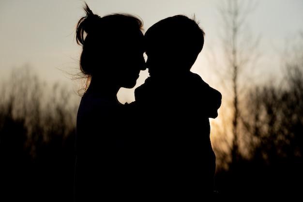 Silhouet van een moeder en zoon die in openlucht bij zonsondergang spelen. moederdag concept