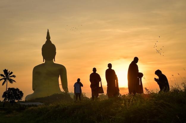 Silhouet van een monnik die 's ochtends een aalmoes gaat halen het is een activiteit die in het boeddhisme moet worden gedaan, op de dag van de boeddhistische vastentijd. in phra nakhon si ayutthaya provincie 24/07/2021