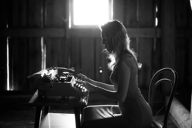 Silhouet van een mooi meisje in een jurk op de achtergrond van een raam in een oud huis