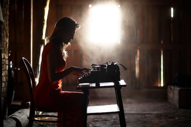 Silhouet van een mooi meisje in een rode jurk op de achtergrond van een raam in een oud huis