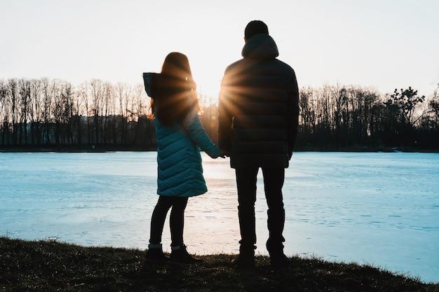 Silhouet van een mooi paar tegen de achtergrond van het meer en de avondlucht in het park.