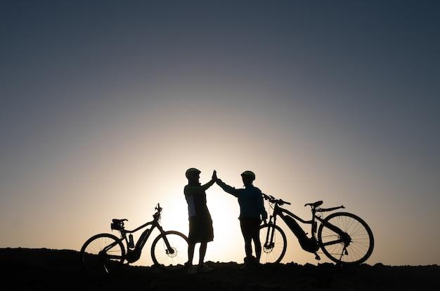 Silhouet van een paar sportieve mensen in de buurt van hun fietsen op de kliffen die genieten van vrijheid en een gezonde levensstijl
