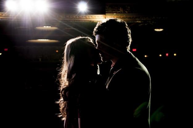 Silhouet van een paar zoenen terwijl ze op het podium in het theater staan