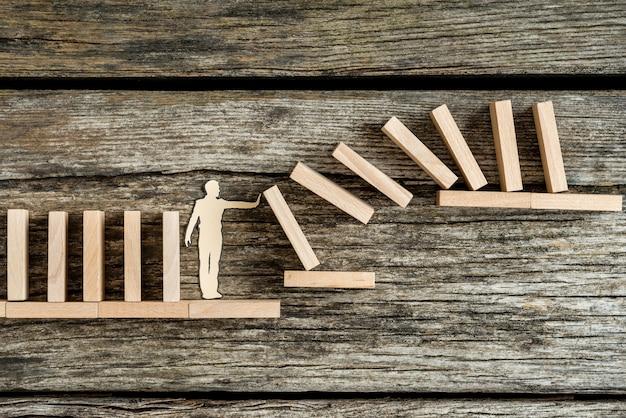 Silhouet van een papieren man tegen het risico van een domino-effect, conceptueel van het oplossen van problemen.