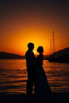 Silhouet van een pasgetrouwd stel op de achtergrond van de ondergaande zon