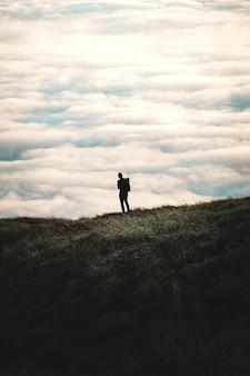 Silhouet van een persoon die op een met gras begroeide heuvel met een bewolkte hemel staat