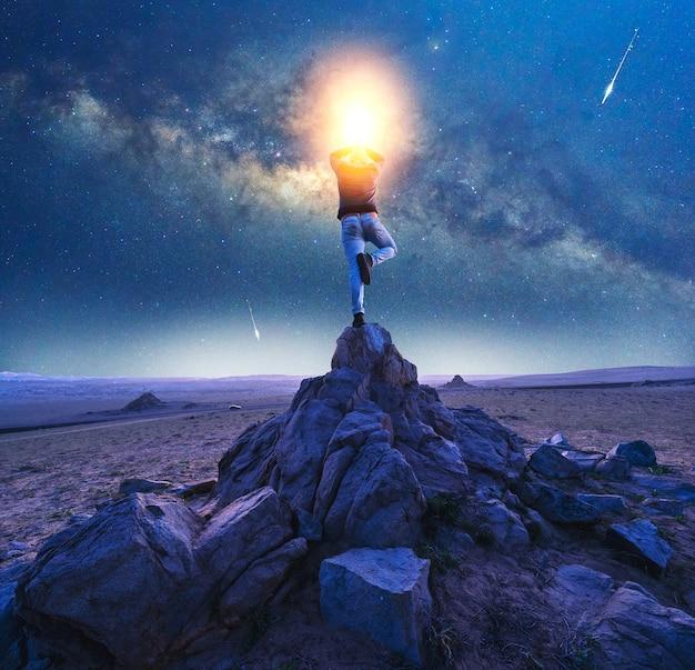 Silhouet van een persoon in de positie van de yogaboom op een rots met melkweg en vallende sterrenachtergrond