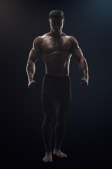 Silhouet van een shirtloze sterke bodybuilder die zich voorbereidt op training dramatische conceptfoto