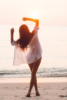 Silhouet van een slank meisje dat zich op een strand met ondergaande zon bevindt. ze draagt een wit overhemd. ze heeft lang haar dat in de lucht vliegt. haar armen strekten zich in de lucht