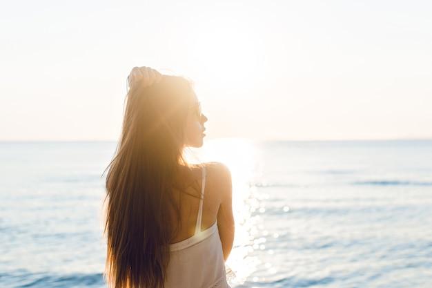 Silhouet van een slank meisje dat zich op een strand met ondergaande zon bevindt. ze draagt een witte jurk. ze heeft lang haar dat in de lucht vliegt. haar armen strekten zich in de lucht