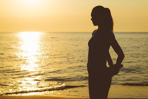 Silhouet van een slanke vrouw op het strand tijdens de ochtendoefening.