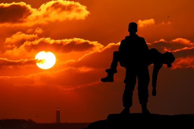 Silhouet van een soldaat officier man die op handen meisje vrouw. het concept van oorlog, slachtoffer