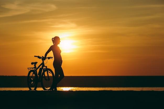 Silhouet van een sportief meisje in een pak dat in de buurt van een fiets staat