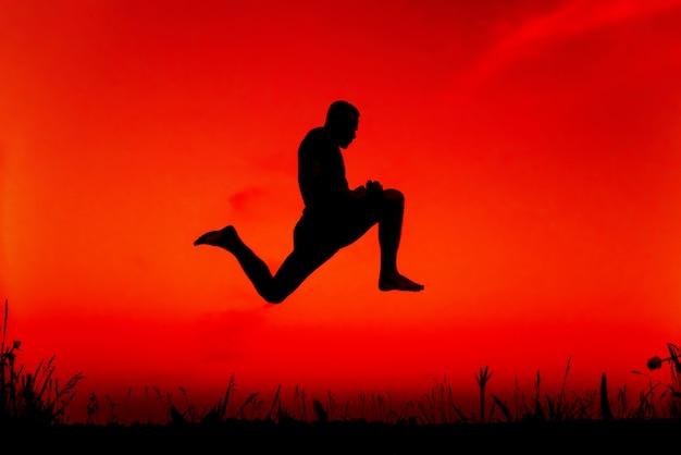 Silhouet van een sportieve man springen hoog in de natuur
