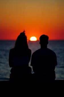 Silhouet van een stel dat geniet van de prachtige zonsondergang aan de kust van de zee