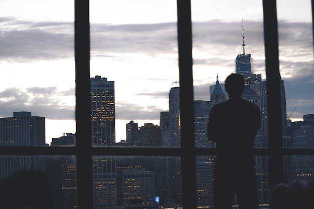 Silhouet van een succesvolle mannelijke status van een raam met uitzicht op het eiland manhattan
