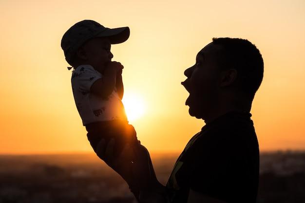 Silhouet van een vader die zijn baby steunt.