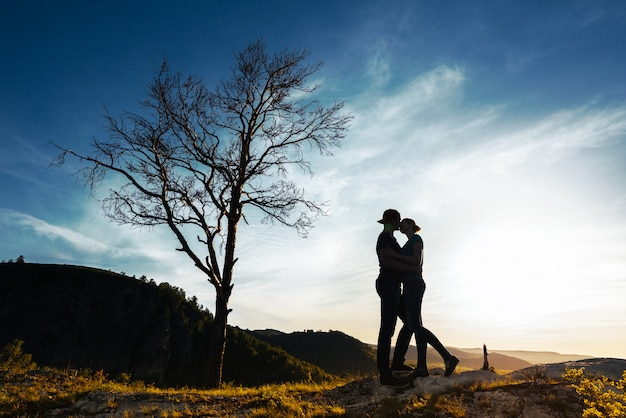 Silhouet van een verliefd paar. jongen en meisje knuffelen bij zonsondergang. echtpaar reist. liefhebbers in de natuur. man en vrouw die op de zonsondergang letten. liefhebbers bij zonsondergang. reis in de bergen. huwelijksreis