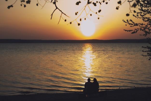 Silhouet van een verliefd stel zittend op een bankje