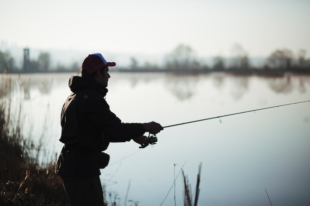 Silhouet van een visser die op meer vist