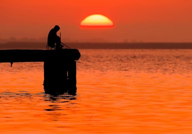 Silhouet van een visser in de stralen van de rijzende zon en zacht rood licht