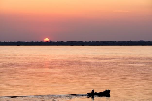 Silhouet van een visser in zijn boot bij zonsondergang