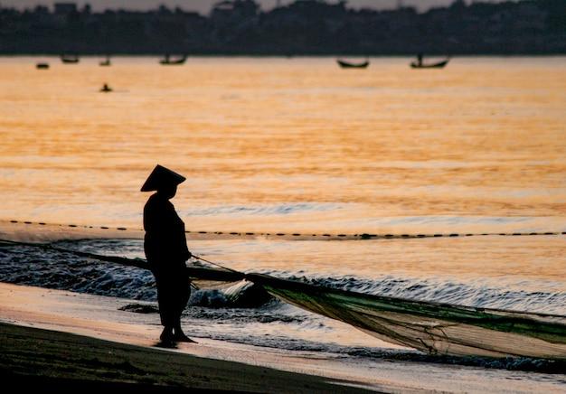 Silhouet van een visser met een boot op een kust