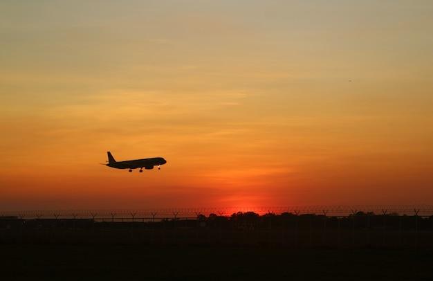 Silhouet van een vliegtuig dat opstijgt tot aan de zonsopganghemel