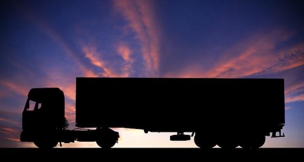Silhouet van een vrachtwagen op weg bij zonsondergang