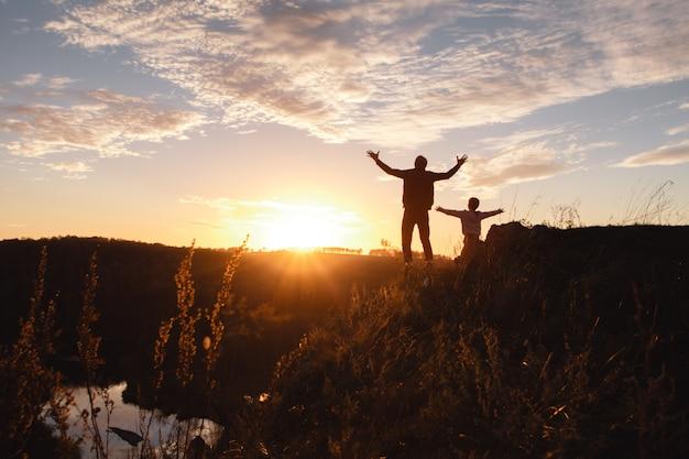 Silhouet van een vrije man en een kind die van vrijheid genieten, die gelukkig bij zonsondergang voelen.