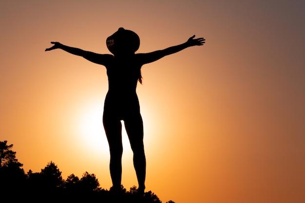 Silhouet van een vrouw bij zonsondergang die een hoed draagt concept van kracht en overwinnen ruimte kopiëren
