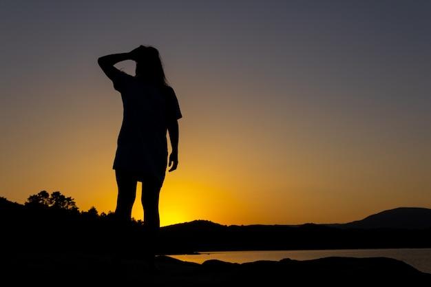 Silhouet van een vrouw bij zonsondergang die naar de horizon kijkt de moeilijkheden van het leven overwinnen ruimte kopiëren