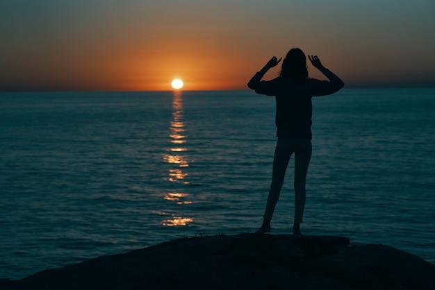 Silhouet van een vrouw bij zonsondergang in de buurt van de zee, gebaren met de handen achteraanzicht