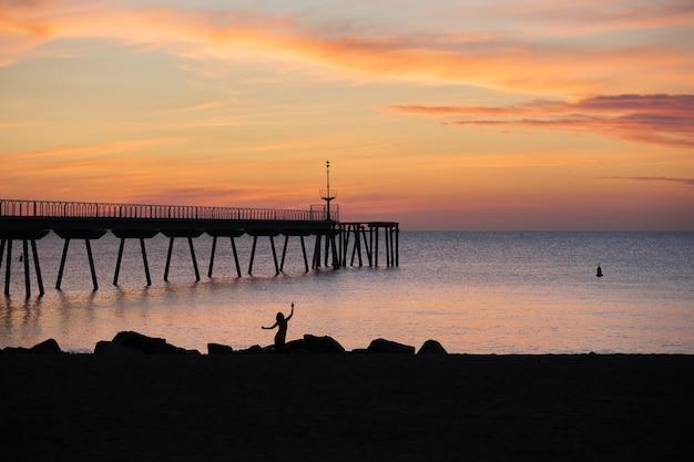 Silhouet van een vrouw die danst op het strand in de ochtendzonsopgang in de middellandse zee met uitzicht op het ponton