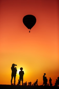 Silhouet van een vrouw die een smartphone houdt die ballon neemt